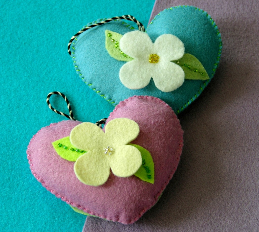 blue and pink felt heart ornaments decorated with flowers
