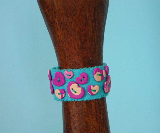 blue button cuff with purple and white hearts